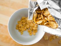 Cornflakes cereal breakfast from the bag to the bowl. royalty free stock images