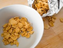 Cornflakes cereal breakfast from the bag to the bowl. royalty free stock photo