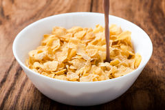Cornflakes cereal pouring chocolate milk on wood table Royalty Free Stock Image
