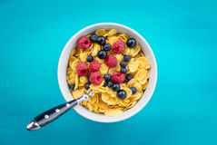 Cornflakes cereal with raspberries and bilberries and black currant in a white bowl. On the blue wooden table Royalty Free Stock Image
