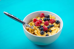 Cornflakes cereal with raspberries and bilberries and black currant in a white bowl. On the blue wooden table Stock Images