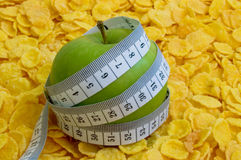 Cornflakes com a maçã com fita de medição Fotografia de Stock Royalty Free