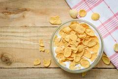 Cornflakes dans la cuvette avec le fond en bois de lait pour le petit déjeuner sain de nourriture de céréale photographie stock libre de droits
