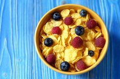 Cornflakes and different Berries - Blueberries and fresh Raspber. Ries, blue wooden background. Good breakfast Royalty Free Stock Photography
