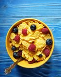 Cornflakes and different Berries - Blueberries and fresh Raspberries, blue wooden background. Good breakfast Royalty Free Stock Photos