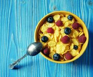 Cornflakes and different Berries - Blueberries and fresh Raspberries, blue wooden background. Good breakfast. Cornflakes and different Berries - Blueberries and Royalty Free Stock Image