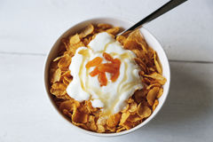 Cornflakes in een kom met yoghurt en honing stock afbeelding