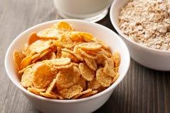 Cornflakes et farine d'avoine dans des cuvettes blanches avec du lait Images libres de droits