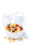 Cornflakes with fresh berries in a bowl, milk, isolated. On white Stock Photo