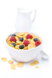 Cornflakes with fresh berries and milk, isolated. Cornflakes with fresh berries and jug of milk, isolated on white Stock Photos