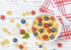 Cornflakes with fresh berries raspberry and blueberry. In white bowl on the table. Healthy Breakfast. Selective focus. Top view Royalty Free Stock Images
