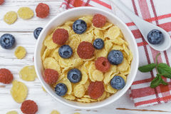 Cornflakes with fresh berries raspberry and blueberry. In white bowl on the table. Healthy Breakfast. Selective focus. Top view Royalty Free Stock Photos
