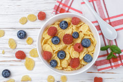Cornflakes with fresh berries raspberry and blueberry. In white bowl on the table. Healthy Breakfast. Selective focus. Top view Stock Photos