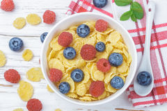 Cornflakes with fresh berries raspberry and blueberry. In white bowl on the table. Healthy Breakfast. Selective focus. Top view Royalty Free Stock Photo