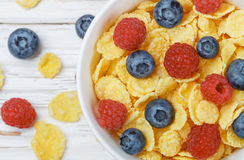 Cornflakes with fresh berries raspberry and blueberry. In white bowl on the table. Healthy Breakfast. Selective focus. Top view Stock Photography