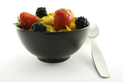 Cornflakes and Fruit in a Black Bowl with a Spoon Royalty Free Stock Images