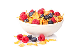 Cornflakes with fruits. A bowl of cornflakes with fruits on white background. Shallow depth of field Royalty Free Stock Photography