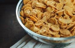 Cornflakes i bunke på tabellen med handduken royaltyfri fotografi