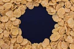 Cornflakes op een zwart graan als achtergrond stock foto's