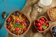 Cornflakes and other cereals with fresh fruits of raspberries, blueberries and milk. On healthy breakfast. Above view Royalty Free Stock Images
