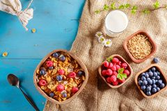 Cornflakes and other cereals with fresh fruits of raspberries, blueberries and milk on healthy breakfast. Above view Royalty Free Stock Photography