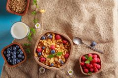 Cornflakes and other cereals with fresh fruits of raspberries, blueberries and milk on healthy breakfast. Above view Stock Photo