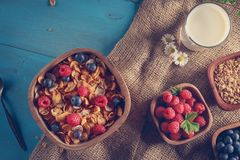 Cornflakes and other cereals with fresh fruits of raspberries, blueberries and milk on healthy breakfast. Above view Royalty Free Stock Images
