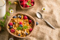 Cornflakes and other cereals with fresh fruits of raspberries, blueberries and milk on healthy breakfast.  Stock Image