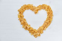 Cornflakes on a painted white wooden background. The symbol of the heart is laid out of cornflakes. Stock Photo