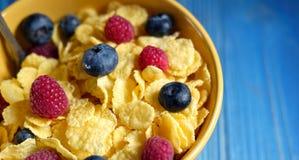 Cornflakes, różne jagody i -, błękitny drewniany tło obrazy royalty free