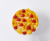 Cornflakes and raspberries. Healthy breakfast - bowl of cornflakes and raspberries in milk Royalty Free Stock Images