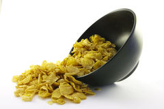 Cornflakes Spilling out of a Bowl Royalty Free Stock Photography