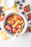 Cornflakes with strawberries and blueberries in a bowl on white background, top view stock image