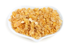 Cornflakes in white dish. Dry cornflakes in heart dish Royalty Free Stock Images