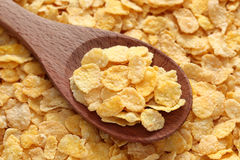 Cornflakes in a wooden spoon. On cornflakes background. Close-up Stock Photos