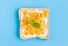 Cornflakes on Yogurt on Bread with Peppermint on Blue Pastel Background Flatlay Medium Shot. Cornflakes on Yogurt on Bread with Peppermint on Blue Pastel royalty free stock photo