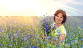 Cornflower field at sunset girl with a bouquet. Beautiful teenager girl in summer field with cornflower stock photos