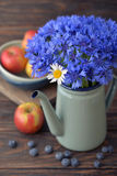Cornflowers with camomile. In  kettle with apples on wooden background closeup Royalty Free Stock Photo
