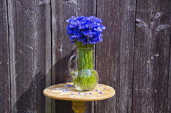 Cornflowers in a jug placed by the wooden wall outdoors Royalty Free Stock Image