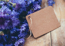 Cornflowers. Rustic bouquet of blue cornflowers and brown cardboard tag on vintage wooden board stock photo