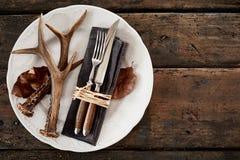 Corni dei cervi con la coltelleria sul piatto Fotografie Stock