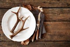 Corni dei cervi sul piatto con la coltelleria contro la tavola Fotografie Stock Libere da Diritti
