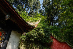 Cornice of ancient Chinese building in woods on sunny day Stock Photos