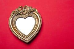 Cornice del cuore dell'oro su colore rosso immagini stock libere da diritti