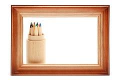 Cornice di legno e matite colorate su bianco Fotografie Stock