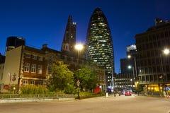 Cornichon et une rue à Londres la nuit images stock