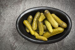 Cornichons in Black Dish on Slate Top View Royalty Free Stock Images
