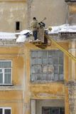 Cornicione della casa di pulizia di neve e di ghiaccio Fotografia Stock Libera da Diritti