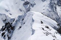 Cornicione della neve in alte montagne di inverno nel giorno piacevole del sole Fotografie Stock