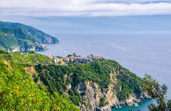 Corniglia traditional typical Italian village with colorful buildings on rock cliff and Manarola, Genoa Gulf, Ligurian Sea, blue s. Ky background, National park stock photos